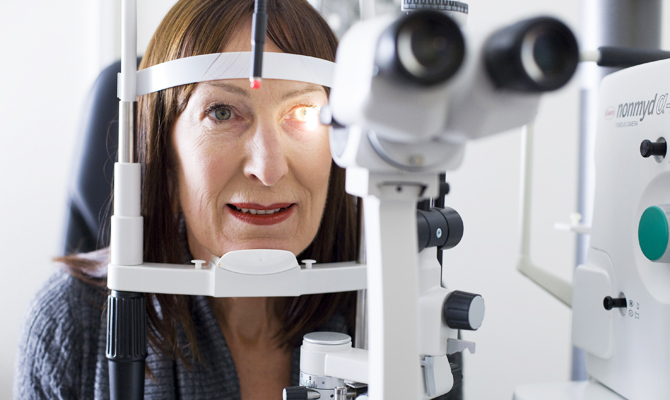 Photo taken from the perspective of an optometrist examining a woman's eyes. The foreground shows artificial light from the slit lamp shining into a woman's left eye.