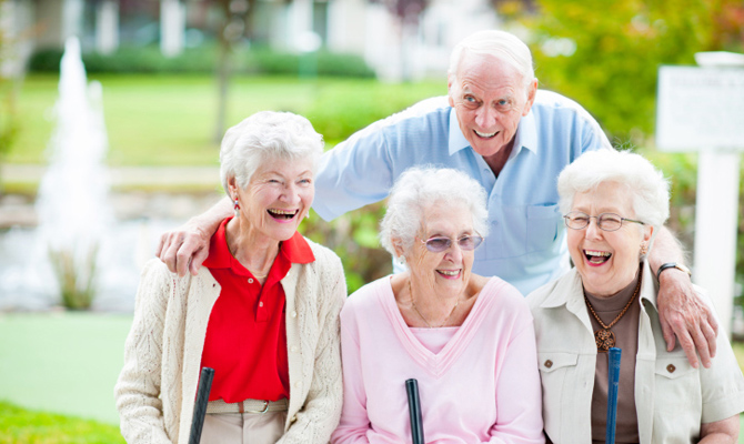 A group of elderly friends pose happily for a photo
