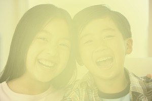 A portrait of two children smiling. Image is cloudy/blurry to illustrate the impact of cataracts on vision.