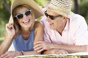 Woman and man both wearing a hat and sunglasses and laughing