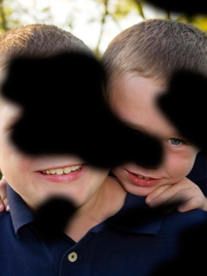 PPortrait of two children smiling. The image is covered with black 'floating clouds' to illustrate the impact of diabetic retinopathy on vision.