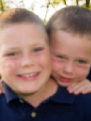 Portrait of two children smiling. The image is blurry to illustrate the impact of refractive error on vision.
