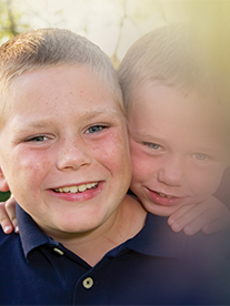Portrait of two children smiling. The image is surrounded by a black faded border which encroaches on the children's faces to illustrate the impact of glaucoma on vision.