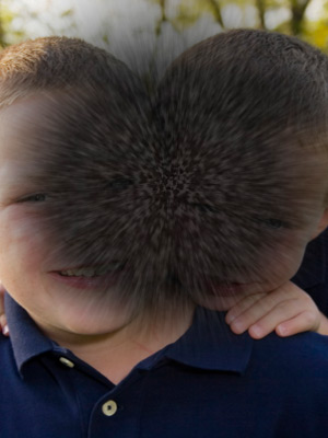 A portrait of two children smiling. The centre of the image is covered by a dark patch which makes faces difficult to see. This is to illustrate the impact AMD could have on vision.