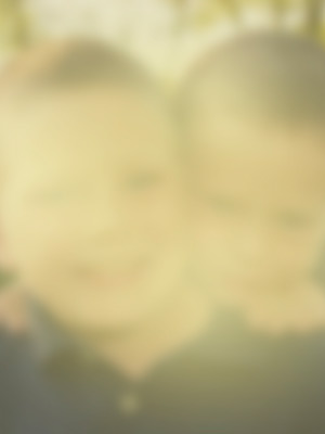 Portrait of two children smiling. The image is cloudy, blurry and covered with a 'yellow stain' to illustrate the impact of cataracts on vision.